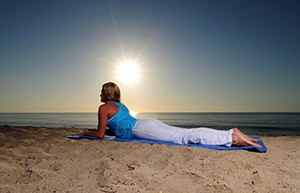 Woman doing sphinx yoga pose on beach during a beautiful sunrise